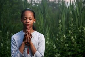 Teenage girl praying outdoors at twilight. Shallow DOF.